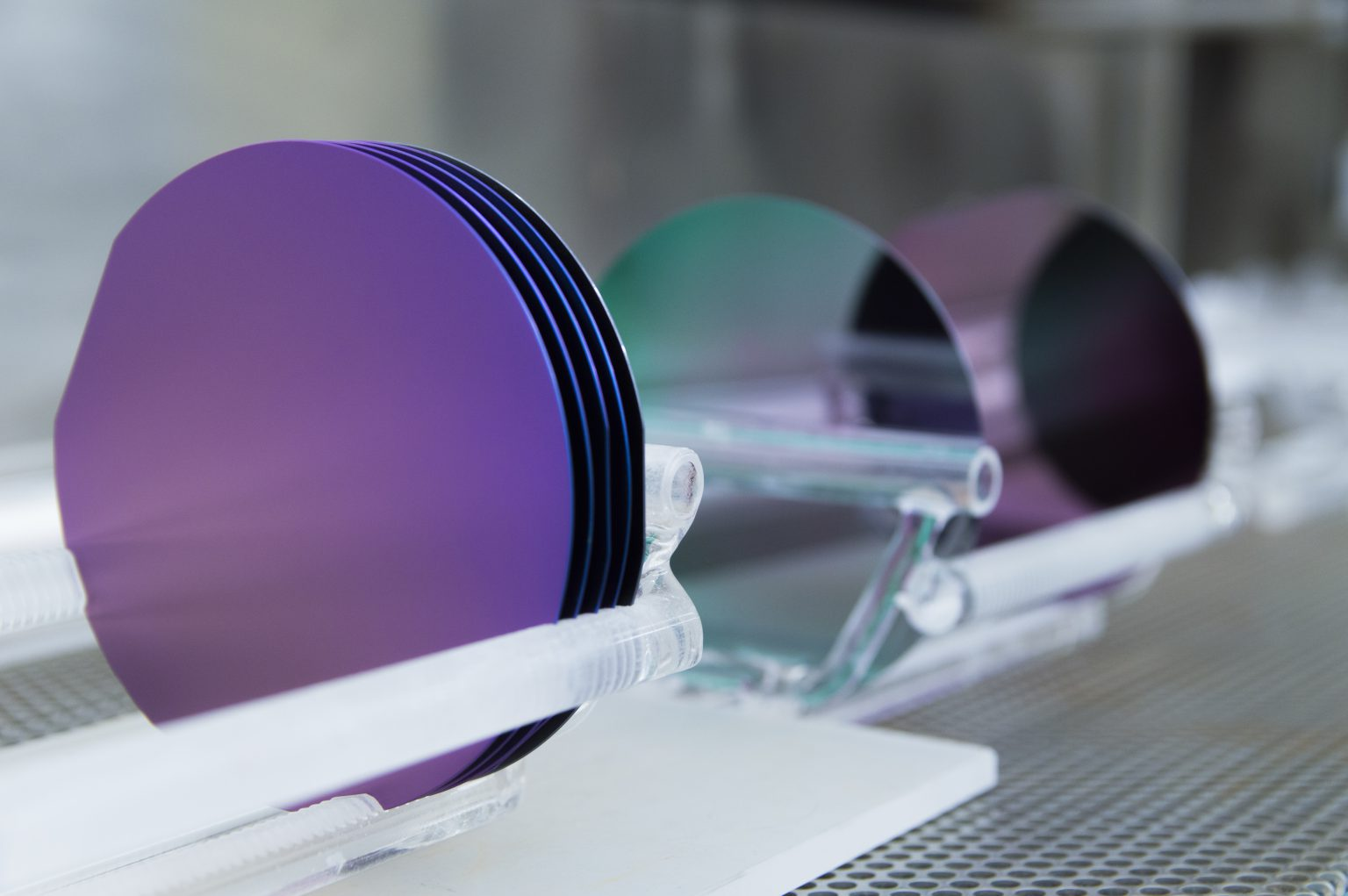 This is a set of 100 mm silicon wafers grown in a cleanroom facility.  They are sitting in quartz holders or boats after being in a silicon dioxide growth furnace.  The high heat from the furnace combined with oxygen converts the surface of the wafers to silicon dioxide.  The wafer colors are dictated by the thickness of the silicon dioxide layer and the viewing angle.  The purples and greens shown on these wafers are quite common and give the cleanroom a colorful and artistic touch.
